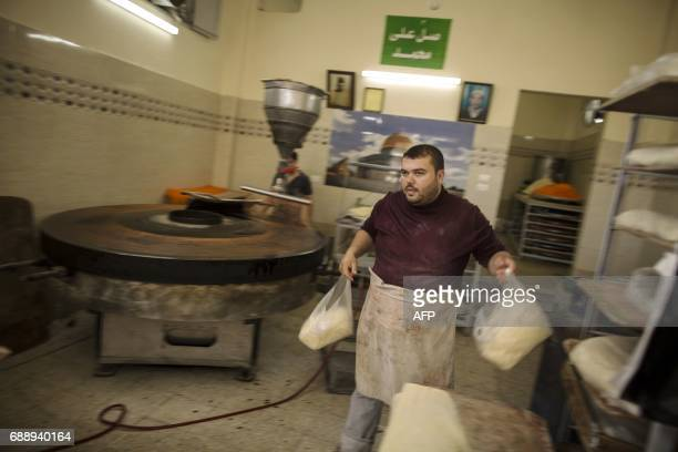 A Palestinian man prepares 'Kunafa' a traditional Arabic sweet on the first day of fasting of the Muslim holy month of Ramadan in Gaza City on May 27...