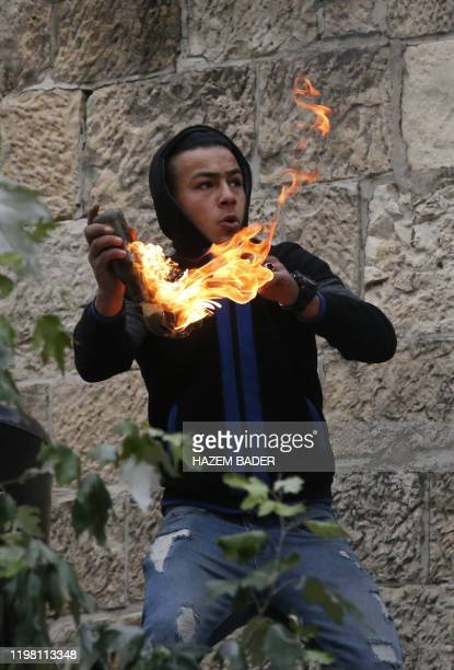 A Palestinian man prepares to throw a molotov cocktail toward Israeli troops during clashes with them at a protest against the USbrokered proposal...