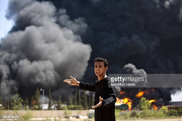 A Palestinian man reacts as flames engulf the fuel tanks of the only power plant supplying electricity to the Gaza Strip after it was hit by...