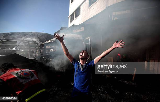 Palestinian man reacts next the wreckage of a minibus after it was hit by an Israeli strike in Gaza City on July 31 2014 At least two people were...