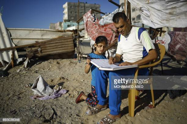 A Palestinian man reads a copy of the Koran Islam's holiest book during the holy Muslim fasting month of Ramadan with a young girl outside his home...