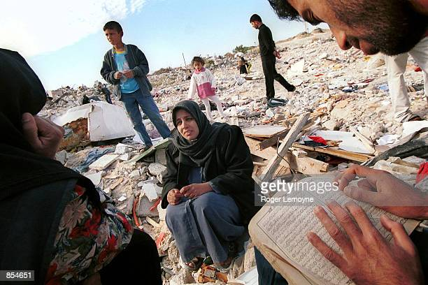 Palestinian man reads from the Koran he salvaged from the rubble of his house as other Palestinians examine the debris of their homes that we razed...