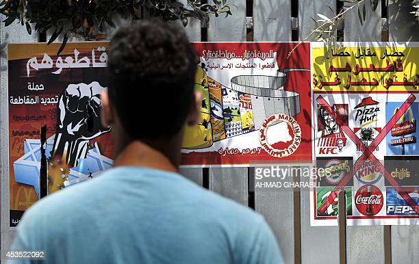A Palestinian man reads posters calling people to boycott Israeli products following the latest war between Hamas militants in the Gaza Strip and...