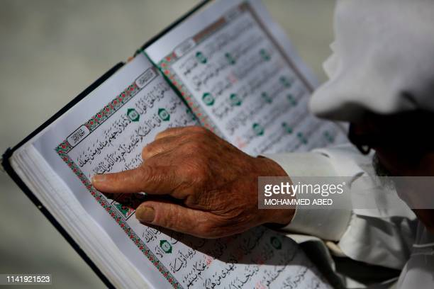 A Palestinian man reads the Koran at the alOmari mosque in Gaza City on the second day of the Muslim holy fasting month of Ramadan on May 7 2019