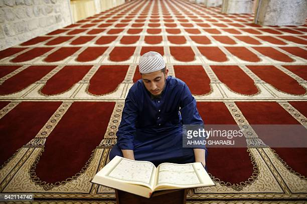 A Palestinian man reads the Koran inside the alAqsa Mosque considered the third holiest site for Muslims after Mecca and Medina during a hot summer...