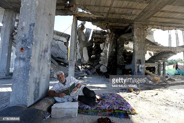 A Palestinian man reads the Koran Islam's holy book during the Muslim holy fasting month of Ramadan in his house destroyed during 50day war between...