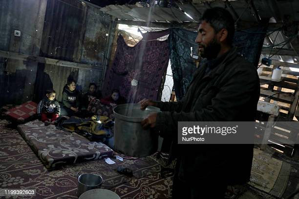 Palestinian man removes a basin filled with water from a leaking roof inside his family tent made of tin and nylon sheets, as children huddle in a...