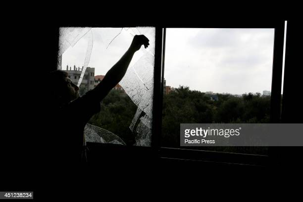 Palestinian man removes shattered glass from a window following an Israeli air strike on Khan Yunis, in the central Gaza Strip. The Israeli air force...