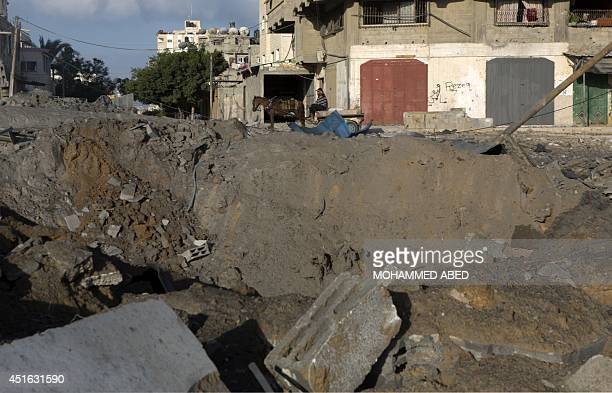A Palestinian man rides a donkey cart past a crater following an overnight Israeli air strike on July 3 2014 in Gaza City Last night Israel launched...