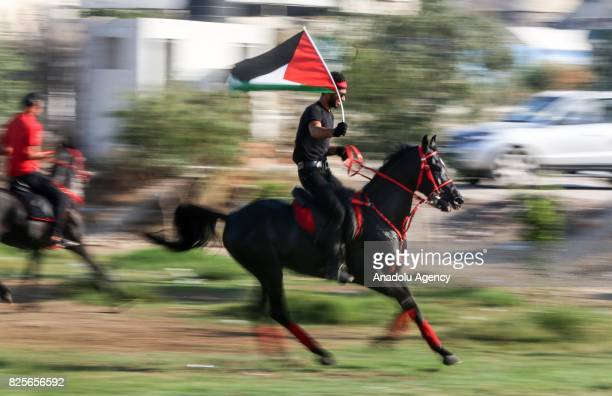 Palestinian man rides a horse as he holds a Palestinian flag during a demonstration organized by Palestine Equestrian Federation to show solidarity...