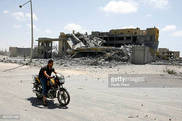 Palestinian man riding a motorcycle drives pass a destroyed governmental prison after an Israeli air strike in Rafah in the southern Gaza Strip The...