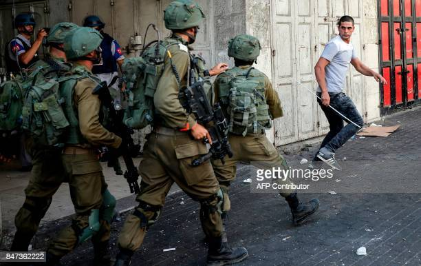 A Palestinian man runs during a demonstration as Israeli soldiers try to catch him in the West Bank city of Hebron on September 15 2017 Israel has...
