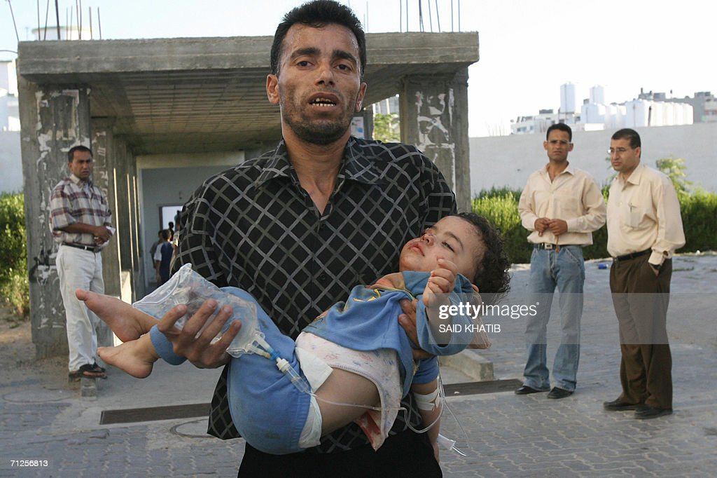 A Palestinian man rushes with an injured : Fotografía de noticias