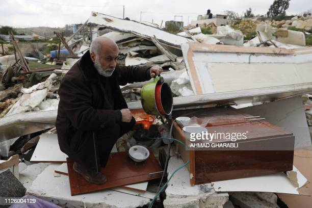Palestinian man salvages some of his belongings from his house that was demolished by Israeli troops in the Arab east Jerusalem neighbourhood of Beit...