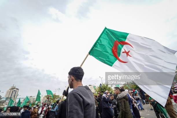 Palestinian man seen holding an Algerian flag during the rally Palestinians take part in a rally marking the 31st anniversary of Hamas' founding