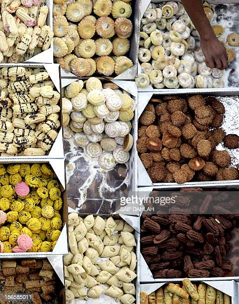 A Palestinian man selects biscuits at a stall as people shop in the West Bank city of Jenin on November 14 ahead of the Muslim holiday of Eid alAdha...