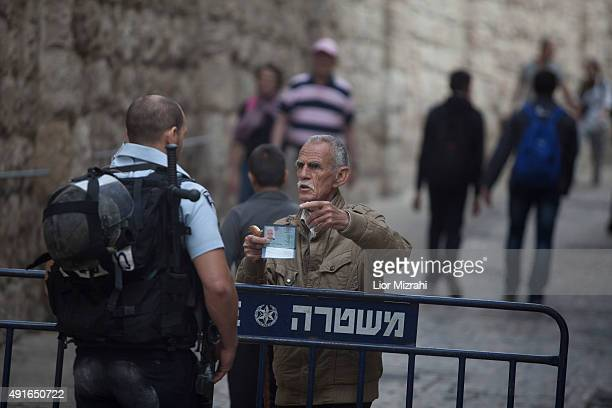 Palestinian man showes his identity card to an Israeli policeman next to a stabbing scene on October 7 2015 in Jerusalem's Old City Israel According...
