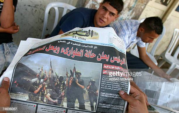 Palestinian man shows off the front page of the AlQuds Arabic daily broadsheet with headlines in red on a black background that read ' The President...
