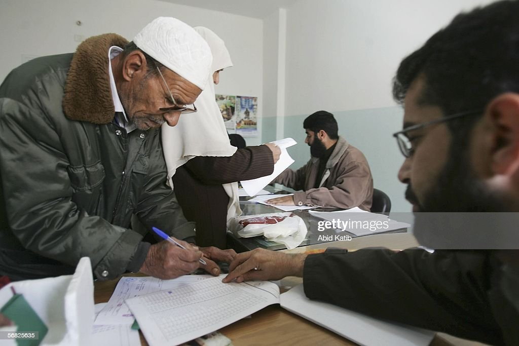 A Palestinian man signs to receive aid money for needy