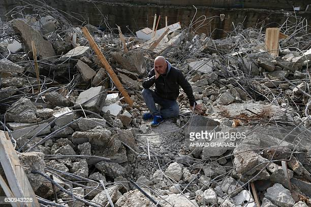 Palestinian man sits amid the rubble of a house that was demolished by Israeli army bulldozers in the Arab east Jerusalem neighbourhood of Beit...