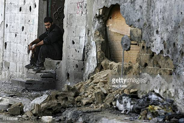 Palestinian man sits in front of his damaged home after Israeli tanks fired on homes in Beit Hanoun November 8 2006 in Beit Hanoun in the northern...
