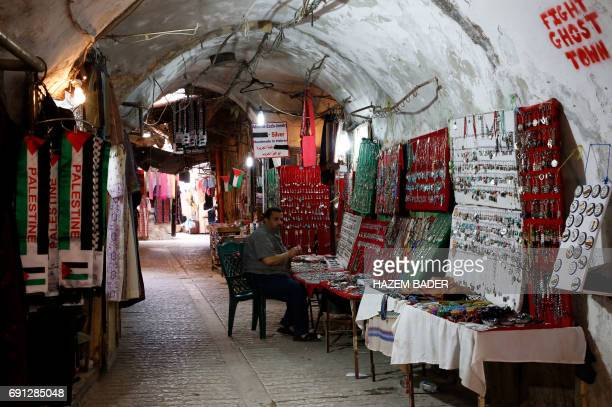 A Palestinian man sits in the old city of the West Bank city of Hebron on May 8 2017 After half a century of occupation Hebron remains an anomaly in...