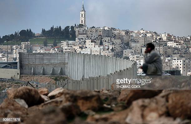 Palestinian man sits near Israel's controversial separation barrier dividing the Palestinian neighbourhood of Al-Tur in the Israeli annexed East...