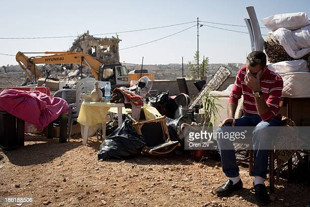 Palestinian man sits next to his belongings as the Jerusalem municipality workers demolish a residential building in an East Jerusalem neighborhood...