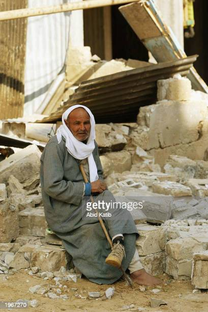Palestinian man sits next to the rubble of his destroyed house May 2, 2003 in the Rafah refugee camp, Gaza Strip. Israeli troops backed by tanks,...
