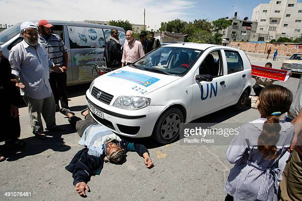 Palestinian man 'sleeps' in front of an United Nations car during a protest in front of the UNRWA headquarters against their decision to reduce aid...