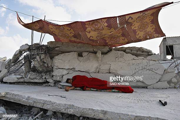Palestinian man sleeps on the rubble of his house which was demolished by Hamas security forces in Rafah in the southern Gaza Strip on May 19, 2010....