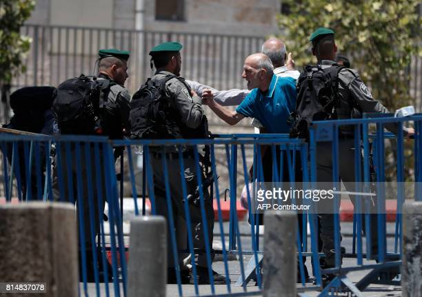 A Palestinian man speaks with an Israeli border police standing guard outside Damascus Gate a main entrance to Jerusalem's Old City on July 15 after...