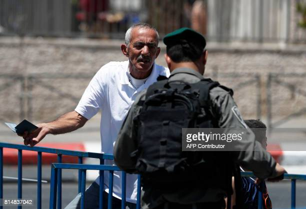 A Palestinian man speaks with an Israeli border policeman standing guard outside Damascus Gate a main entrance to Jerusalem's Old City on July 15...