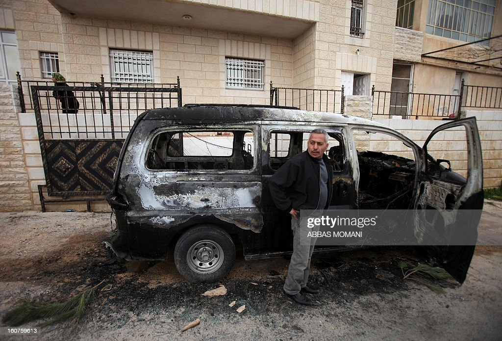 A Palestinian man stands next to a burnt vehicle following an apparent price tag attack by Jewish settlers in the West Bank village of Deir Jarir, northeast of Ramallah, on February 5, 2013. Suspected Jewish extremists torched a vehicle and scrawled Hebrew graffiti on a nearby wall in the village, Palestinians and Israelis said.