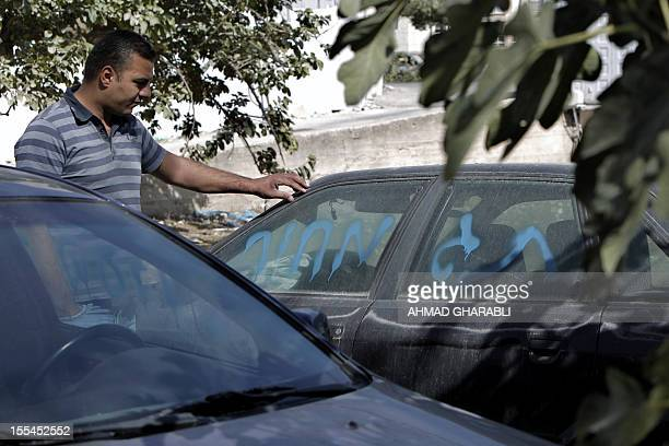 """Palestinian man stands next to a car with a graffiti which reads in Hebrew ,""""Price tag"""" in the Palestinian neighborhood of Shuafat, in Israeli..."""