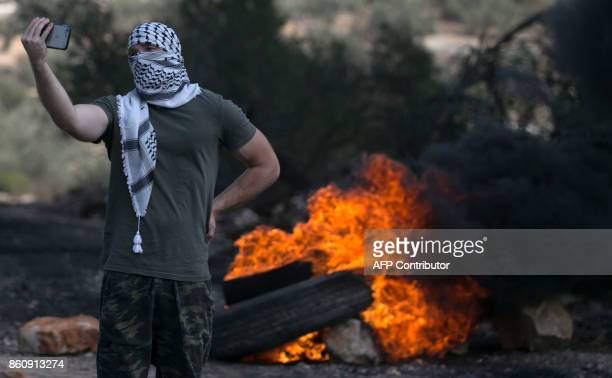 A Palestinian man takes a selfie during clashes with Israeli security forces following a weekly demonstration against the expropriation of...