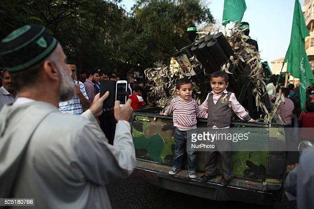 Palestinian man takes picture to his sons on a military truck during a parade for militants of the Ezzedine al-Qassam brigade, the armed wing Hamas...