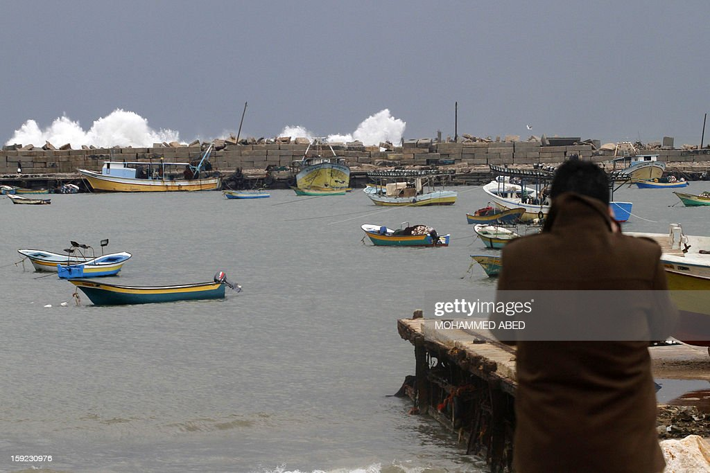 A Palestinian man takes pictures of giant waves on January 10, 2013 in Gaza City. In Gaza, cold weather and heavy rain flooded several of the tunnels running between the territory and Egypt as in the West Bank city of Ramallah, children and adults, including some policeman stopped their cruiser for an impromptu snowball fight.