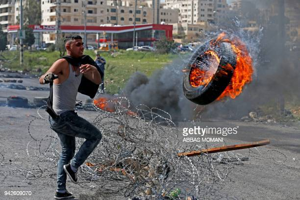 A Palestinian man throws a burning tire during a protest in the West Bank city of Ramallah on April 6 2018 Clashes erupted on the GazaIsrael border...