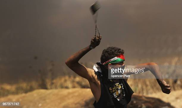 Palestinian man throws a rock towards the border fence with Israel as mass demonstrations at the fence continue on May 11 2018 in Gaza City Gaza One...