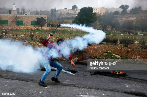 Palestinian man throws a tear gas canister back towards Israeli security forces during clashes following the weekly Muslim Friday prayers in the West...