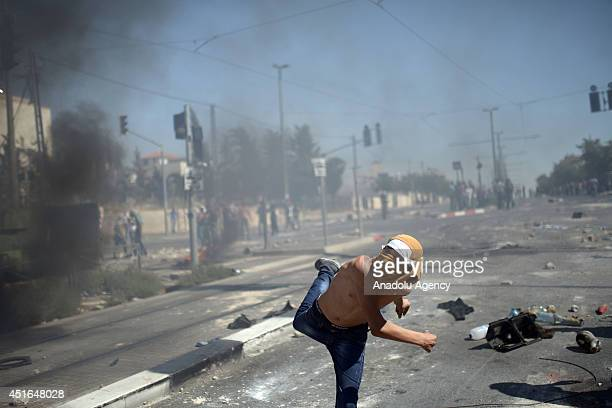 Palestinian man throws stone at Israeli security forces during the clashes over the abduction and killing of a Palestinian teen by suspected Jewish...