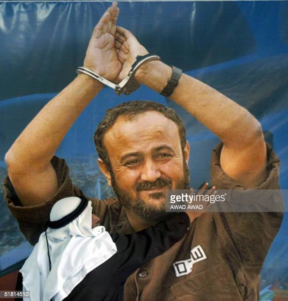 Palestinian man touches a giant poster of Fatah's jailed leader and Palestinian Authority presidential candidate Marwan Barghuti at his electoral...