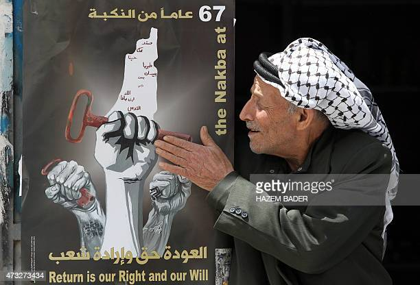 A Palestinian man touches a poster displayed on a door annoucing the commemorations for the 67th anniversary of the 'Nakba' on May 14 2015 at the...