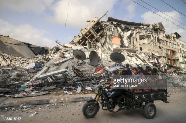 Palestinian man transports children in a tricycle past the Al-Shuruq building, destroyed by an Israeli air strike, in Gaza City on May 21 after a...