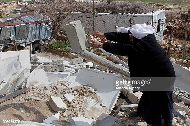 Palestinian man tries to clear the debris of his house which was demolished by Israeli authorities on the ground that the house was unauthorized in...