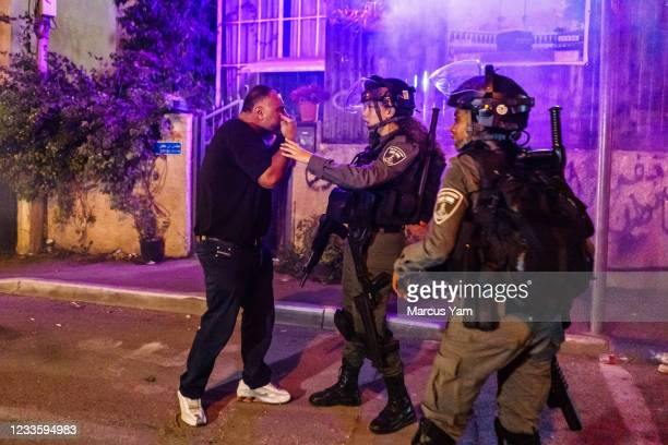 Palestinian man tries to talk sense as Israeli police officers try to disperse the crowd that broke into brawl, in the Sheikh Jarrah neighborhood in...