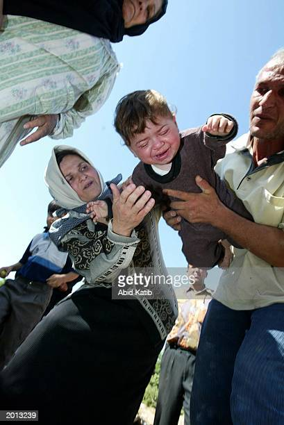 Palestinian man tries with his wife to treat their oneyearold sick baby Motaz AlZaanen as they wait for an ambulance May 19 2003 at Beit Hanoun town...