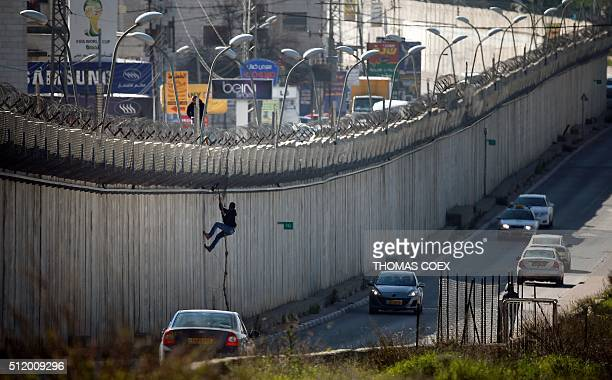 Palestinian man uses a rope to climb over a section of Israel's controversial separation barrier that separates the West Bank city of alRam from east...
