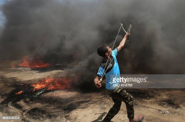 Palestinian man uses a slingshot during clashes with Israeli forces along the border with the Gaza strip east of Khan Yunis on May 14 as Palestinians...
